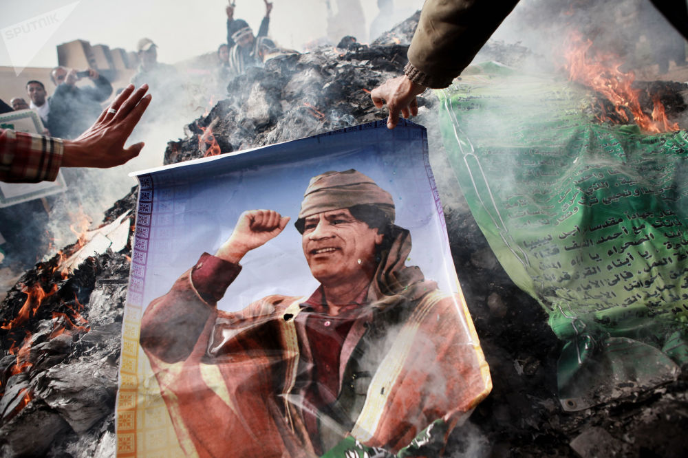 班加西居民焚烧卡扎菲肖像、卡扎菲名言标语和卡扎菲的《绿皮书》。