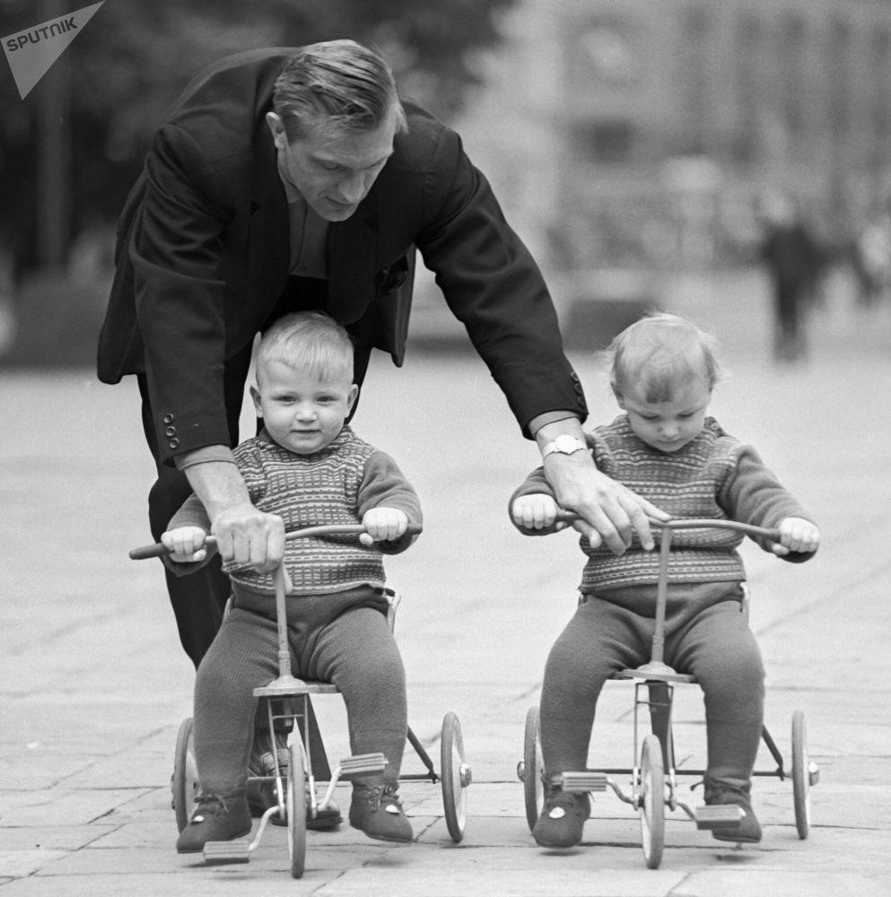 一名父亲在教双胞胎宝宝骑三轮自行车。1968年。