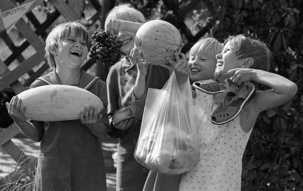 塔什干一家孤儿院中手提怀抱香瓜、西瓜、葡萄和桃的学生们,这些都是在孤儿院院子里种植的水果。1983年。