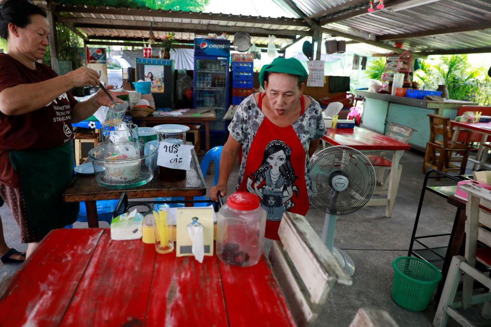 泰国曼谷街头的商贩在看被抓的放到塑料瓶中的眼镜蛇。