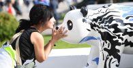 """一名女孩在莫斯科全俄展览中心举行的""""中国:伟大遗产和新时代""""中国文化节大熊猫雕塑展上。"""