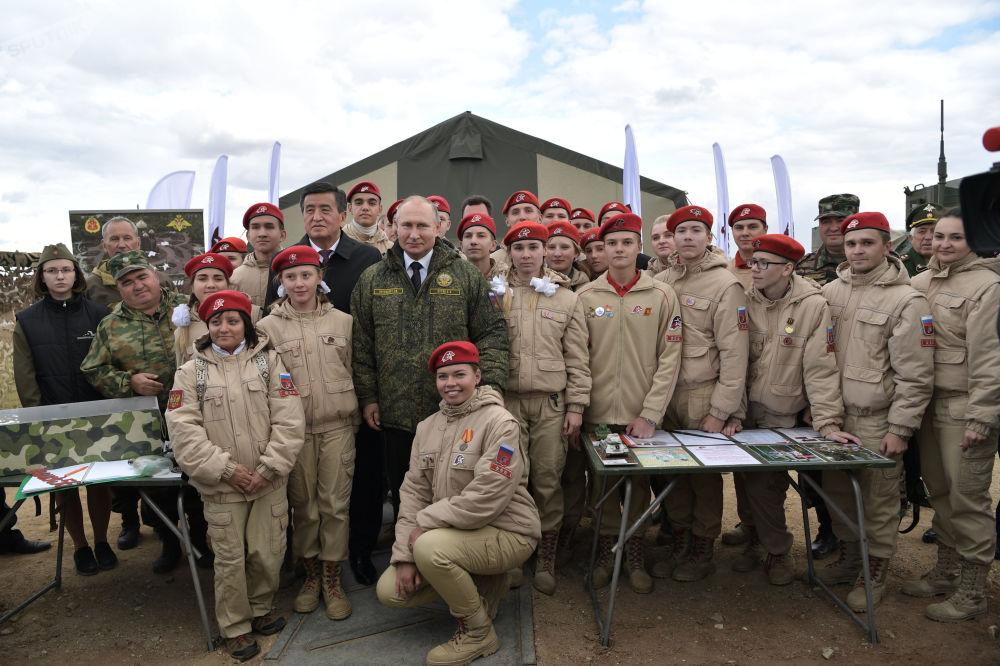 """弗拉基米尔·普京和索伦贝·热恩别科夫在栋古兹训练场与全俄青少年军事爱国主义组织""""青年军""""的参加者们合影。"""