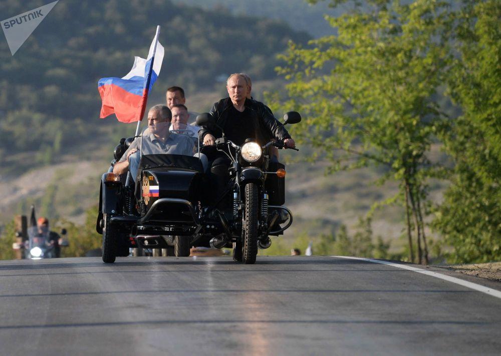 2019年8月10日,俄罗斯联邦总统普京在塞瓦斯托波尔举办的巴比伦的影子国际车展上驾驶一辆乌拉尔牌三轮偏斗摩托车。此次车展由夜狼摩托车俱乐部主办。左边是克里米亚共和国领导人,部长会议主席谢尔盖·阿克肖诺夫。