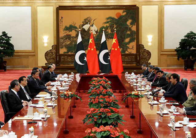 Pakistan's Prime Minister Imran Khan chats with Chinese Premier Li Keqiang during a signing ceremony at the Great Hall of the People in Beijing