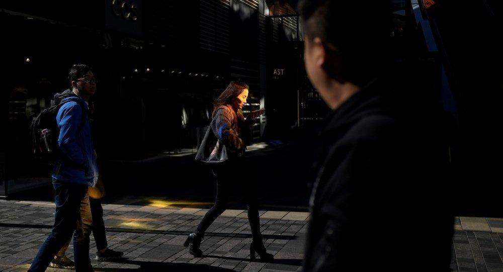 Женщина с телефоном на улице Пекина