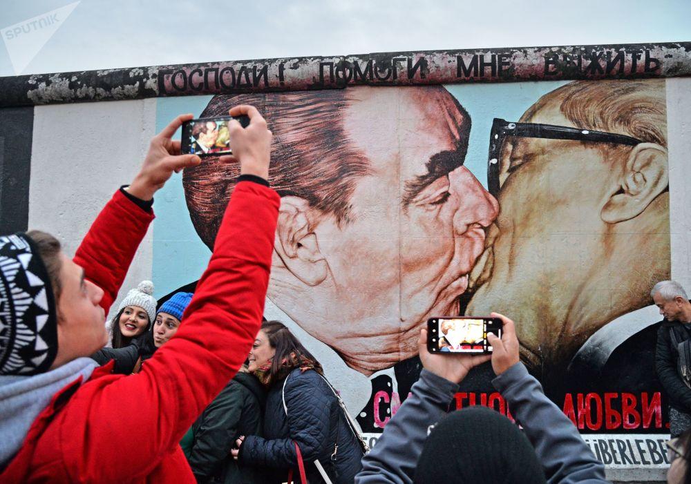 人们在磨坊街(Mühlenstrasse)柏林墙艺术作品展示区Dmitri Wrubel绘制的《我的上帝,助我在这致命之爱中存活》或称《兄弟之吻》的画作旁
