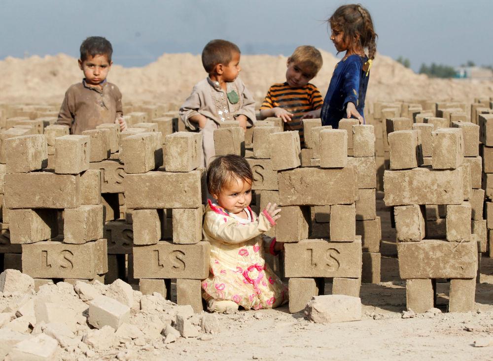 在贾拉勒阿巴德郊外砖厂内玩耍的阿富汗儿童。